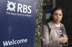 Вывеска рядом с отделением Royal Bank of Scotland в Лондоне. Royal Bank of Scotland в пятницу сообщил о резком росте убытков в первом квартале финансового года и выразил неуверенность относительно сроков возвращения к выплате дивидендов в связи с низким доходом, расходами на реструктуризацию и вялой продажей активов.  REUTERS/Neil Hall