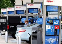 A motorist fills up at an Exxon service station in a file photo. REUTERS/Stelios Varias
