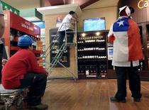 Empleados de un supermercado miran un partido de fútbol, en La Serena, Chile. 15 de junio de 2015. Las ventas reales del comercio minorista (ICVM) en Chile y de los supermercados mostraron débiles expansiones en marzo, en medio de una débil demanda interna, un deterioro del mercado laboral y un desfavorable efecto calendario. REUTERS/Marcos Brindicci