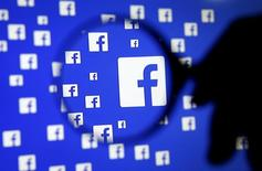 Un accionista de Facebook Inc presentó el viernes una propuesta de demanda colectiva con el objetivo de detener el plan de la compañía de emitir nuevas acciones de Clase C, al considerar que se trata de una decisión injusta para afianzar el control del presidente ejecutivo, Mark Zuckerberg. En esta ilustración fotográfica realizada en Bosnia-Herzegovina se aprecia el logo de Fcebook aumentado por el lente de una lupa, 16 dic, 2015. REUTERS/Dado Ruvic