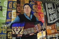 Женщина продает текстиль на рынке в Ашхабаде 8 февраля 2012 года. Международный валютный фонд ждет замедления роста зависящей от цен на газ экономики Туркмении до 5,4 процента с 6,5 процента в 2015 году, сообщил фонд после визита своей миссии в страну. REUTERS/Aman Mehinli