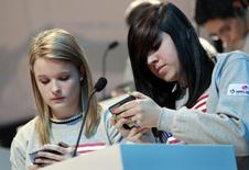 Kate Moore (L) and Morgan Dynda of the U.S. compete in the LG Mobile Worldcup Texting Championship in New York, January 14, 2010. REUTERS/Mike Segar/File Photo