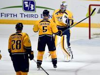 Nashville Predators goalie Pekka Rinne (35) celebrates with defenseman Barret Jackman (5) after a win against the San Jose Sharks in game three of the second round of the 2016 Stanley Cup Playoffs at Bridgestone Arena. The Predators won 4-1. Mandatory Credit: Christopher Hanewinckel-USA TODAY Sports
