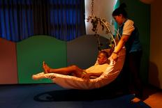 An elderly man receives help from a nurse during a physical therapy session at Bangkhae Home Foundation in Bangkok, Thailand, April 27, 2016. REUTERS/Athit Perawongmetha