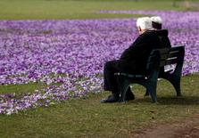 An elderly couple sit on a bench next crocus flowers in a park in Duesseldorf March 17, 2010.  REUTERS/Ina Fassbender