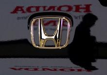 A visitor and the logo of Honda Motor Co are reflected on a Honda car at the company's headquarters in Tokyo January 30, 2009.      REUTERS/Toru Hanai/File Photo         GLOBAL BUSINESS WEEK AHEAD PACKAGE - SEARCH 'BUSINESS WEEK AHEAD MAY 9'  FOR ALL IMAGES - RTX2DEBZ