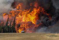 Smoke and flames from the wildfires erupt behind a car on the highway near Fort McMurray, Alberta, Canada, May 7, 2016. REUTERS/Mark Blinch