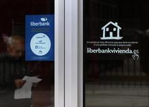 Liberbank va a proponer a sus representantes sindicales un nuevo plan de ajuste que podría afectar a unos 600 trabajadores, alrededor del 15 por ciento de su plantilla, según información de CSIF, el mayor sindicato de funcionarios en España. En la imagen, un hombre lee unos papeles en una sucursal de Cajastur, del grupo Liberbank en Oviedo, el 22 de mayo de 2014. REUTERS/Eloy Alonso