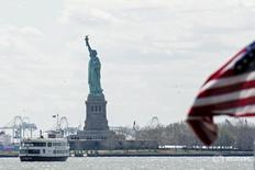 """Флаг США на фоне статуи Свободы в Нью-Йорке 24 апреля 2015 года. Что может быть более американским по духу, чем стоять на заднем дворе своего дома в День памяти, делая барбекю с бутылкой пива в руке? Budweiser уверен, что нашел ответ - пиво должно называться """"Америка"""". REUTERS/Lucas Jackson"""