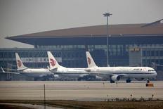 Самолеты компании Air China в международном аэропорту Пекина. Китай инвестирует около 4,7 триллиона юаней ($724 миллиарда) в проекты, связанные с транспортной инфраструктурой, в течение следующих трёх лет, сказано в докладе, опубликованном на сайте министерства транспорта страны в среду.  REUTERS/Kim Kyung-Hoon