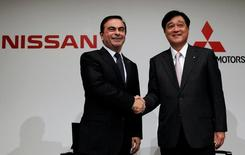 Nissan Motor's Chief Executive Carlos Ghosn (L) shakes hands with Mitsubishi Motors Corp.'s President Osamu Masuko at the end of their joint news conference in Tokyo December 14, 2010. REUTERS/Toru Hanai/File Photo