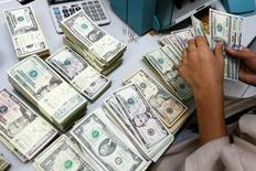 Банковский служащий пересчитывает доллары США в Бангкоке. Доллар достиг двухнедельного пика к корзине основных валют в пятницу, поскольку американская статистика укрепила уверенность, что ФРС может поднять ставки в текущем году более одного раза. REUTERS/Athit Perawongmetha