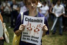 Una mujer sostiene un cartel en protesta al Tratado de Libre Comercio entre Estados Unidos y Colombia, en Washington. 11 de julio de 2011. Sindicatos colombianos y estadounidenses dijeron que el Gobierno de Bogotá fracasó en el cumplimiento de la protección a los trabajadores como fue establecido en un acuerdo de libre comercio bilateral, lo que ha levantado dudas sobre cláusulas similares en un pacto panamericano más amplio. REUTERS/Molly Riley