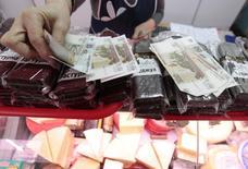 Продавщица демонстрирует рублевые купюры на рынке в Ставрополе 21 января 2016 года. Центробанк РФ видит сохранение проинфляционных рисков в краткосрочной перспективе, допускает временный рост годовой инфляции в мае-июне из-за эффекта низкой базы, ожидая возобновления ее снижения с июля, говорится в обзоре, подготовленном ЦБР. REUTERS/Eduard Korniyenko