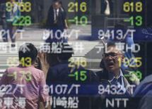 Personas se reflejan en un tablero electrónico que muestra información bursátil, en una correduría en Tokio, Japón. 18 de abril de 2016. Las bolsas de Asia se recuperaban el martes desde mínimos en dos meses, luego de que un rebote en las acciones del gigante tecnológico Apple Corp y las ganancias en los precios del petróleo impulsaron a Wall Street. REUTERS/Toru Hanai
