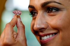 "A model poses with ""The Unique Pink"" diamond mounted during a preview at Sotheby's auction house in Geneva, Switzerland May 9, 2016.  REUTERS/Denis Balibouse"