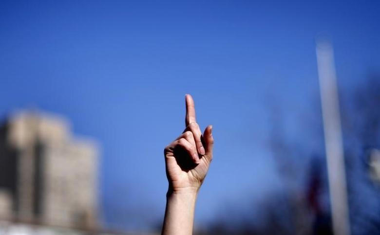 A woman raises a finger to the air as she dances with others to the theme song of the ''One Billion Rising'' campaign in New York City's Washington Square Park on Valentines Day February 14, 2013. REUTERS/Mike Segar