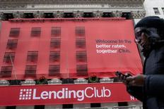 A woman looks at her phone as she passes by a Lending Club banner on the facade of the the New York Stock Exchange December 11, 2014. REUTERS/Brendan McDermid