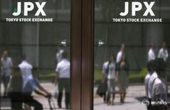 Люди отражаются в дверях здания Токийской фондовой биржи 11 июня 2015 года. Ведущий фондовый индекс Японии Nikkei закрылся почти без изменений в четверг, колеблясь в ходе торгов между ростом и снижением, на фоне общей настороженности инвесторов, которая нивелировала подъём после публикации протоколов последнего заседания ФРС, спровоцировавшей укрепление доллара и ослабление иены. REUTERS/Thomas Peter
