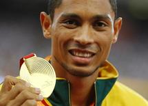 Wayde van Niekerk of South Africa presents his gold medal as he poses on the podium after the men's 400 metres final during the 15th IAAF World Championships at the National Stadium in Beijing, China, August 27, 2015.   REUTERS/Damir Sagolj