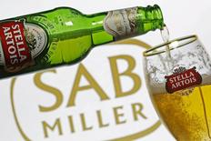 Photo illustration of beer flowing from a bottle of Stella Artois into a glass, seen against a SAB Miller logo, November 5, 2015.   REUTERS/Dado Ruvic/File Photo