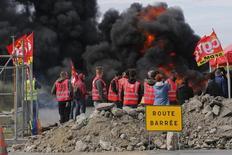 Empleados sindicalizados de la petrolera francesa Total, parados frente a una barricada que bloquea la entrada a depósitos cerca de la refinería de Donges. 19 de mayo de  2016. La petrolera francesa Total detuvo la producción en tres refinerías del país por las protestas contra una reforma a la ley laboral que incluyeron el bloqueo de depósitos y de estaciones de servicio, dijo el sábado la asociación de la industria UFIP. REUTERS/Stephane Mahe