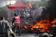 La petrolera francesa Total detuvo la producción en tres refinerías del país por protestas contra la reforma laboral que incluyeron el bloqueo de depósitos y de estaciones de servicio, dijo el sábado la asociación de la industria UFIP. Imagen de las protestas de los trabajadores del gigante francés Total en la que se observa a un manifestante lanzando un neumatico a una barricada para bloquear la entrada de un depósito de la compañía cerca de la refinería de Donges, Francia, el 19 de mayo 2016.  REUTERS/Stephane Mahe