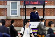 Los ministros de Finanzas del Grupo de los siete países más desarrollados (G7) ratificaron los pactos cambiarios existentes, incluyendo el compromiso de no buscar tipos de cambio específicos y evitar devaluaciones competitivas, mostró un resumen oficial divulgado el martes. En la imagen, un policía japonés vigila una estación de tren desde un stand con un panel sobre la cumbre del G7, en Tokio, el 16 de mayo de 2016. REUTERS/Thomas Peter