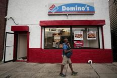 A man walks in front of a Domino's pizza restaurant in Hoboken, New Jersey July 8, 2015.  REUTERS/Eduardo Munoz
