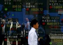 Un hombre camina junto a un panel que muestra el Nikkei y otros índices de mercado, afuera de una correduría en Tokio, Japón. 19 de abril de 2016. Las acciones japonesas subieron el viernes en un débil volumen de negocios, en medio de las expectativas cada vez mayores de que el primer ministro, Shinzo Abe, retrasaría en varios años un aumento del impuesto sobre las ventas fijado para abril del próximo año. REUTERS/Thomas Peter