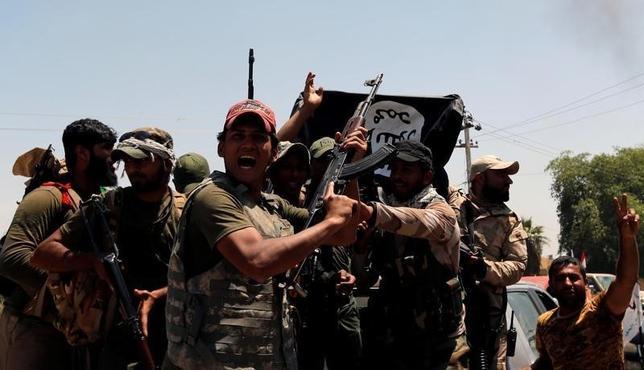 5月23日、多くの専門家は現在、過激派組織「イスラム国(IS)」が終焉(しゅうえん)を迎えつつあるのではないかと推測している。写真はイラクのガーマでの戦闘で勝利し、ISの旗を掲げるシーア派の戦闘員。26日撮影(2016年 ロイター/Thaier Al-Sudani)