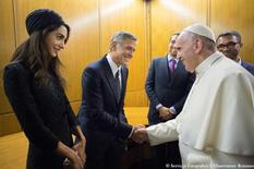 Pope Francis meets U.S. actor George Clooney (C) and his wife Amal (L) during a meeting of the Scholas Occurrentes at the Vatican, May 29, 2016. Osservatore Romano/ Handout via REUTERS