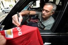 Jose Mourinho signs a Manchester United soccer shirt held out by a fan as he leaves his house in London, Britain, May 27, 2016. REUTERS/Toby Melville