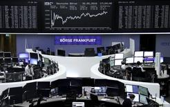 Traders work at their desks in front of the German share price index, DAX board, at the stock exchange in Frankfurt, Germany, May 30, 2016.     REUTERS/Staff/Remote