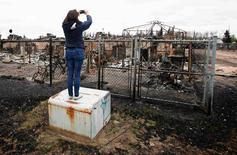 A woman takes photos of the burned remains of a house in the Abasand neighbourhood of Fort McMurray, Alberta, Canada, May 9, 2016.   REUTERS/Chris Wattie/File Photo
