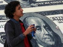 Мальчик проходит мимо рекламы пункта обмена валюты в Каире 21 февраля 2016 года. Доллар держался вблизи максимального значения двух месяцев к корзине основных валют во вторник из-за растущих ожиданий скорого подъёма ставки американским Федрезервом; австралийский доллар резко вырос благодаря неожиданно сильной экономической статистике. REUTERS/Mohamed Abd El Ghany