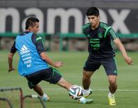 Mexico striker Alan Pulido (R) dribbles the ball past Paul Aguilar during a practice session in Mexico City May 14, 2014. Picture taken on May 14, 2014. REUTERS/Henry Romero/File Photo