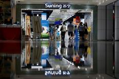 Customers walk past at the entrance to a Suning store in Shanghai, August 26, 2013. REUTERS/Aly Song