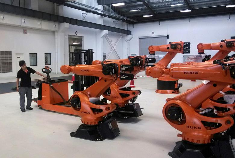 A staff member stands next to robots at a plant of Kuka Robotics in Shanghai, China August 13, 2014. REUTERS/Pete Sweeney/File Photo