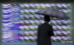 Женщина с зонтом у экрана, демонстрирующего котировки у биржи в Токио 8 сентября 2015 года. Японские акции показали рекордное за месяц однодневное процентное падение в четверг из-за укрепления иены, в то время как глобальные опасения, такие как приближающийся референдум о членстве Британии в ЕС и тревоги о бюджетной политике Японии, ослабили аппетиты к риску. REUTERS/Issei Kato
