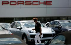 A man walks past various new Porsche models on a dealer's lot in Silver Spring, Maryland, U.S. June 1, 2016. REUTERS/Gary Cameron