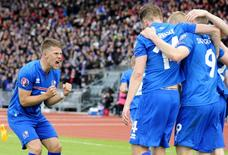 Iceland's Kolbeinn Sigthorsson (number 9) celebrates with teammates and Johann Gudmundsson (L) after scoring against Czech Republic during their Euro 2016 qualifying soccer match in Reykjavik, Iceland, June 12, 2015. REUTERS/Sigtryggur Johannsson/File Photo