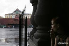 Женщина курит у Красной площади в Москве 7 августа 2007 года. Выходные обещают Москве облачную погоду с прояснениями, дожди и грозы, свидетельствует усреднённый прогноз, составленный на основании данных Гидрометцентра России, сайтов intellicast.com и gismeteo.ru. REUTERS/Denis Sinyakov