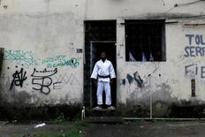 Popole Misenga, a refugee from the Democratic Republic of Congo and a judo athlete, poses at the entrance of his home in a slum in Rio de Janeiro, Brazil, June 2, 2016. REUTERS/Pilar Olivares