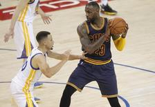 June 2, 2016; Oakland, CA, USA; Cleveland Cavaliers forward LeBron James (23) controls the ball against Golden State Warriors guard Stephen Curry (30) during the first half in game one of the NBA Finals at Oracle Arena. Mandatory Credit: Cary Edmondson-USA TODAY Sports