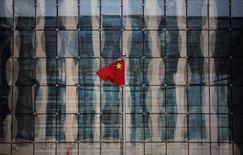 El banco central de China recortó su previsión para las exportaciones el miércoles, pronosticando una segunda caída anual consecutiva en los envíos, pero dijo que la economía todavía crecerá un 6,8 por ciento en 2016. En la imagen, la bandera nacional china ondea en la sede de un banco comercial cerca de la sede del Banco de China en Pekín, el 24 de noviembre de 2014.  REUTERS/Kim Kyung-Hoon