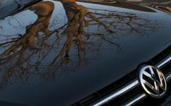 Volkswagen dijo el miércoles que recibió aprobación regulatoria para reparar otros 1,1 millones de automóviles, lo que eleva el número de modelos de la automotriz alemana que están aptos para su reposición en el mercado a más de 2,5 millones de unidades desde el comienzo del año. En la imagen, el capó de un vehículo con el logotipo de Volkswagen tiene reflejado un árbol sobre su carrocería negra, al amanecer en Londres, el 5 de mayo de 2016. REUTERS/Russell Boyce