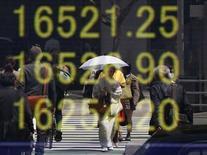 Una mujer en kimono se refleja en un tablero que muestra el índice Nikkei, afuera de una correduría en Tokio, Japón. 18 de abril de 2016. Las acciones japonesas cayeron el jueves luego de que los valores financieros fueron golpeados por una caída en los rendimientos de los bonos globales, mientras que los papeles de los exportadores fueron debilitados por un repunte del yen. REUTERS/Toru Hanai