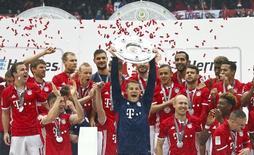 Les joueurs du Bayern Munich célèbrent leur nouveau titre de chamion d'Allemagne. La ligue de football allemande a attribué les droits de diffusion nationale des quatre prochaines saisons de première et deuxième divisions pour un montant total de 4,64 milliards d'euros, le groupe britannique Sky décrochant la majeure partie des lots mis aux enchères. /Photo prise le 14 mai 2016/REUTERS/Michael Dalder