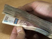 Сотрудник таджикского Агроинвестбанка демонстрирует таджикские сомони в отделении банка в Душанбе 2 февраля 2012 года. Второй по величине кредитор Таджикистана Тоджиксодиротбанк, где регулятор ввел временную администрацию, попросил у Европейского банка реконструкции и развития вклада в капитал, а также помощи правительства. REUTERS/Nozim Kalandarov